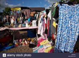 rail of 2nd hand womens clothes for sale at a car boot sale in