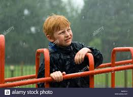boy looking unhappy getting wet in a park in the rain stock photo