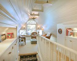 low attic loft room with wicker chairs and wall sconces low