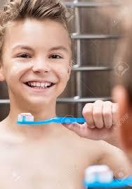 smiling teen boy brushing teeth in bathroom stock photo picture