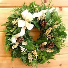 fresh winter wreath decorated w pine cones salal a white ribbon