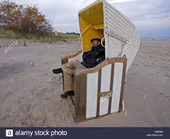 Chairs On A Beach Mr Man In Warm Clothes Sitting In A Beach Chair On A Beach In