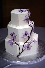 a silver and white wedding cake with lavender sugar flowers by
