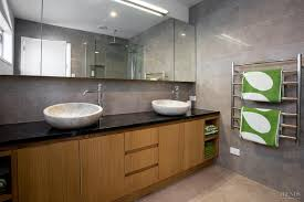 bathroom with timber cabinetry marble basins and granite walls