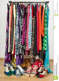 dressing closet with colorful clothes and shoes nicely arranged on