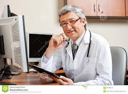 Front Desk Secretary Jobs by Doctor Sitting At Desk In Front Of Computer Stock Photography