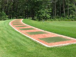 driving range mats set into a curved paver practice tee line the