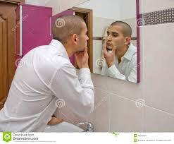 man looking at himself in the bathroom mirror stock photo image