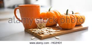 Small Pumpkins Closeup On Small Pumpkins Seeds And Tea Bag On Table Stock Photo