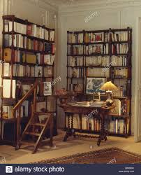 lighted lamp on table in library study with tall bookshelves and