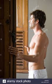 young man opening window shutters stock photo royalty free image