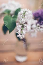 Vase Stands Bouquet Of Lilac In A Vase Stands On The Table Stock Photo