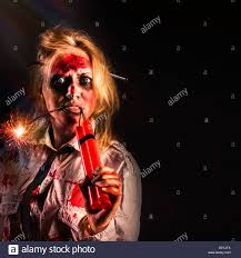 evil female halloween zombie with bloody face holding bomb on