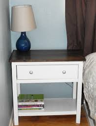 rectangular white wooden bedside table with brown wooden top also