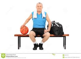 basketball player on bench mature man with basketball sitting on a bench stock image image