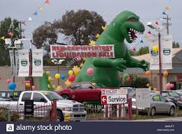 chrysler jeep dodge dealership huge inflated dinosaur among vehicles at the entrance to a