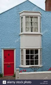 portrait image of a small blue house with a red front door stock