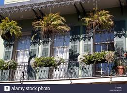 hanging planters and window boxes hanging from a wrought iron