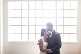 and groom cuddle up in front of soft window light