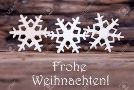 three wooden snowflakes with the german words frohe weihnachten