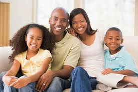 Family Sitting In Living Room Smiling  University Bank - Family in living room