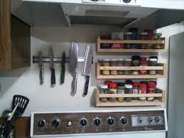 spice racks and a magnetic knife holder above the stove portland
