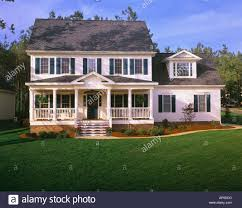 large white two story house with blue shutters a front porch and