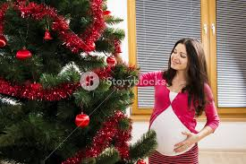 young pregnant woman is decorating christmas tree royalty free
