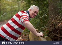 mature man doing push ups against park bench in forest stock photo