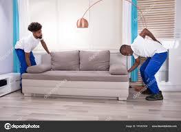 canap mal de dos jeunes mâles déménageurs avec mal dos levage canapé dans salon
