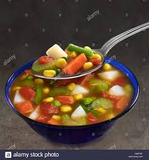 hearty vegetable soup in blue bowl with spoon stock photo royalty