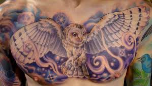blue ink flying owl tattoo on chest