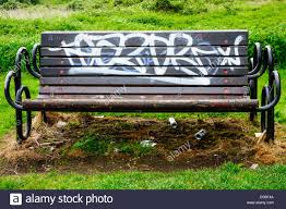 The Bench Graffiti An Empty Park Bench With Graffiti And Empty Beer Cans Scattered