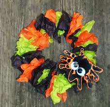 halloween paper plate wreath craft with an adorable hand print