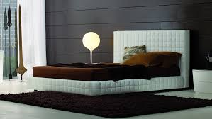 bedroom unique bed design with fabric high headboard and king bed size set with rectangular pattern looks comfortable in front of black brick wall