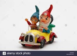 cartoon car back noddy driving his car with big ears and golly sitting in the back