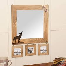 wooden wall mirror with deer detail and photo frames by dibor