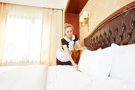 hotel service female housekeeping worker maid making bed with