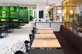 the kitchen at de bijenkorf becomes the buzz of the town news the triangular open seating area next to the glass facade features furniture in a mix of black and natural wood set against a lively green wall