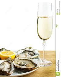 oysters in a white plate with lemon and a glass of wine on a