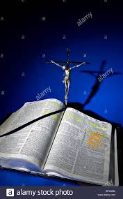 statue of jesus christ on the cross at the top of an open bible