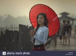 burmese women in burmese traditional dress with red umbrella on u