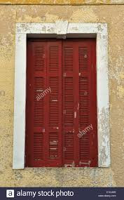 red window shutter and weathered chipped paint wall stock photo