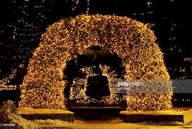 holiday lights decorate the antler arches on the town square of