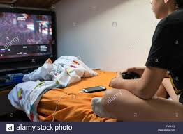 young boy playing video games sitting on the bed in her room while