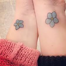 small cute name initial tattoo with forget me not flower tattoos