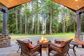 large back yard with grass and covered patio with firepit stock