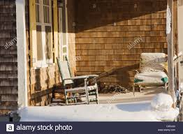 rocking chair and snow on front porch of vacant cottage in winter