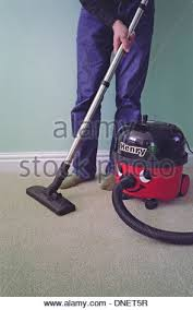 Vaccumming Caucasian Man Vacuuming A Carpet With A Henry Vacuum Cleaner Model