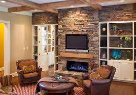 grey stone fireplace with brown wooden mantel shelf connected by